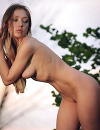 Delightful naked beauty showing off her excellent shapely body outdoor on the riverside.